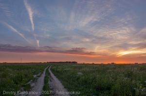 Красивое фото заката с полевой дорогой и деревней на горизонте
