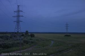 Ночная дорога через поле с вышками ЛЭП